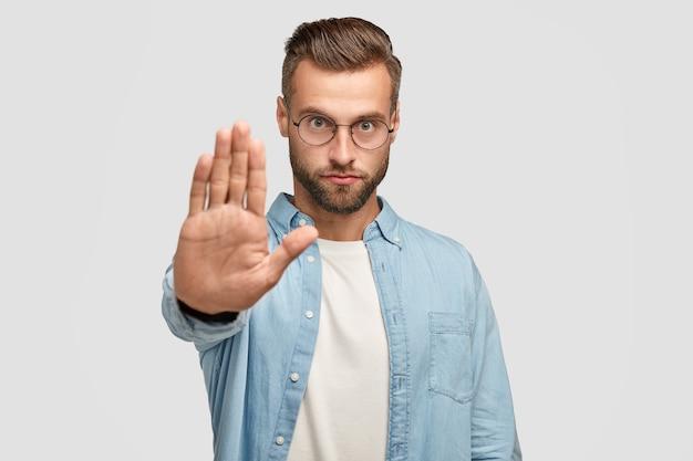 Ernsthafte europäische männliche shows stoppen die geste, fordern etwas, haben einen strengen gesichtsausdruck, tragen eine runde brille und ein formelles hemd, das über einer weißen wand isoliert ist. konzept der menschen- und körpersprache Kostenlose Fotos