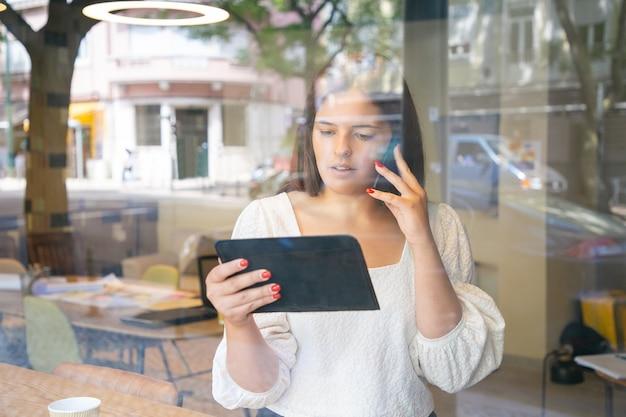 Ernsthafte geschäftsfrau, die auf zelle spricht, tablette benutzt und bildschirm betrachtet Kostenlose Fotos