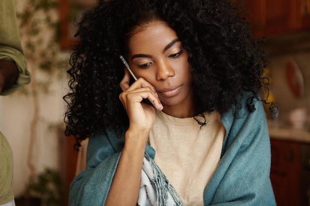 Ernsthafte junge dunkelhäutige frau mit afro-frisur, die besorgten und unglücklichen blick beim sprechen auf dem handy hat Kostenlose Fotos