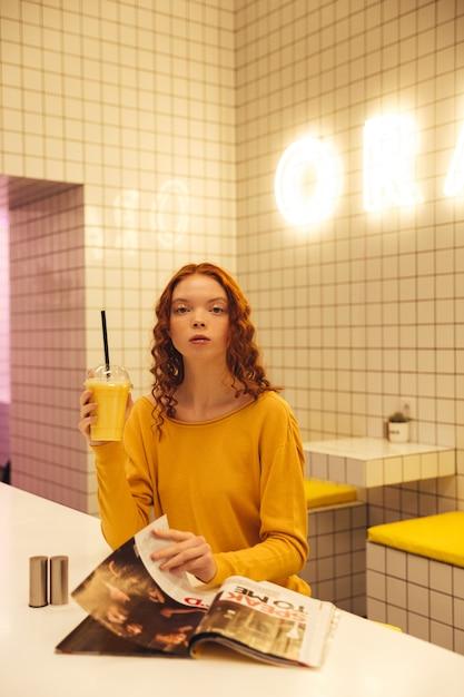 Ernsthafte junge rothaarige lockige dame, die im café sitzt Kostenlose Fotos