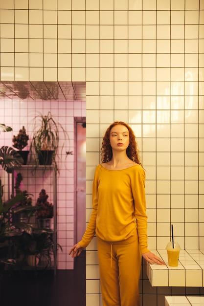 Ernsthafte junge rothaarige lockige dame, die im café steht Kostenlose Fotos