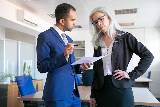 Ernsthafte kollegen diskutieren projektdokument für die unterzeichnung und grauhaarige managerin in brillen hören chef. partner, die im besprechungsraum arbeiten. teamwork-, geschäfts- und managementkonzept Kostenlose Fotos