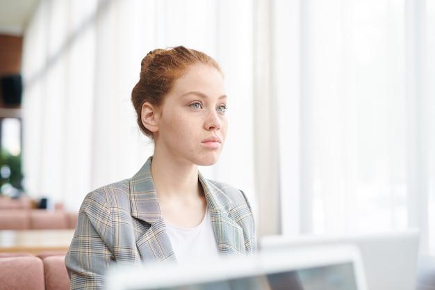Ernsthafte nachdenkliche rothaarige junge dame in karierter jacke, die kollege beim treffen im café zuhört Premium Fotos