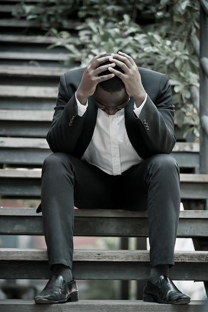Ernsthafter afrikanischer geschäftsmannprofi scheiterte oder war in seinem job verärgert und saß auf einer treppe. geschäftsproblemkonzept. Premium Fotos