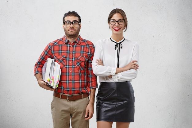 Ernsthafter bärtiger mann mit vielen büchern und seiner schönen weiblichen gruppenkameradin, die ausländische literatur studieren wird Kostenlose Fotos