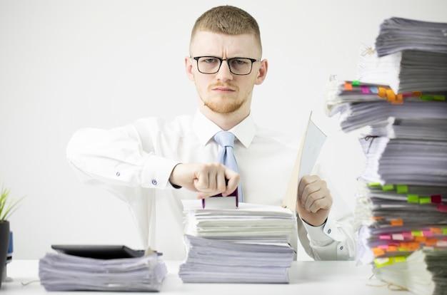 Ernsthafter büroangestellter im hemd mit krawatte und brille sitzt am tisch mit papierkram Premium Fotos