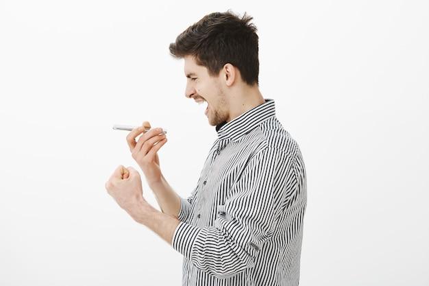Ernsthafter fokussierter junger dunkelhaariger mann, der im profil steht und smartphone nahe mund hält, faust ballt, während er am gerät singt oder über lautsprecher über graue wand spricht, karaoke spielt Kostenlose Fotos