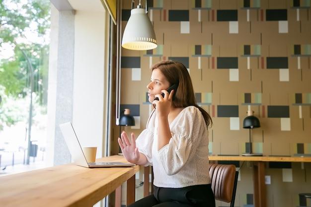 Ernsthafter freiberuflicher fachmann, der am handy spricht, während er am schreibtisch mit laptop und kaffee im gemeinsamen arbeitsraum sitzt Kostenlose Fotos