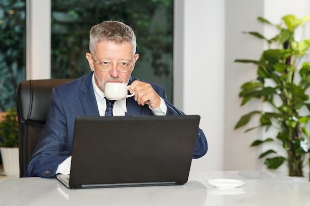 Ernsthafter gealterter geschäftsmann, der morgen-espresso trinkt und nachrichten auf laptop-bildschirm im café liest Premium Fotos