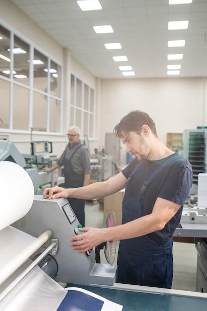 Ernsthafter junger arbeiter in der gesamtstellung an der druckmaschine und auswahl der kopienmenge auf dem bedienfeld Premium Fotos