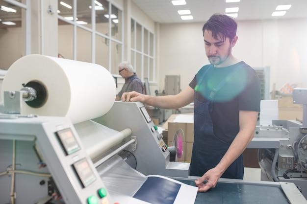 Ernsthafter junger druckspezialist mit bartdruckmaschine beim drucken der testseite im werk Premium Fotos