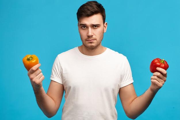 Ernsthafter junger mann mit borsten, der orange und rote paprika mit unentschlossenem gesichtsausdruck hält, zweifel und verdacht hat, will kein pestizidgemüse essen Kostenlose Fotos