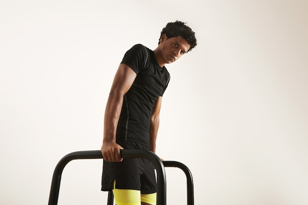 Ernsthafter junger muskulöser afroamerikanischer athlet im schwarzen technischen t-shirt und in den schwarzen und gelben shorts, die dips auf kurzen balken tun, die auf weiß isoliert werden. Kostenlose Fotos
