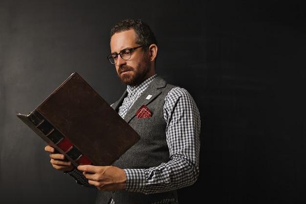Ernsthafter männlicher lehrer in tweedweste und kariertem hemd, das ein großes altes buch an einer tafel liest Kostenlose Fotos