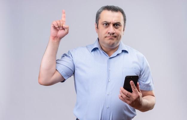 Ernsthafter mann mittleren alters, der blau gestreiftes hemd trägt, das etwas verbietet, indem er seinen zeigefinger hebt und handy in der anderen hand auf einem weißen hintergrund hält Kostenlose Fotos