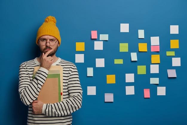 Ernsthafter mentorführer denkt über kreative ideen nach, hält das kinn und schaut direkt in die kamera, trägt eine transparente runde brille und steht mit notizblöcken Kostenlose Fotos