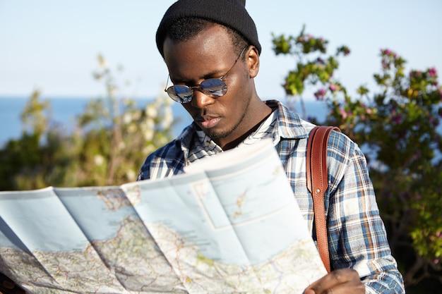 Ernsthafter verlorener europäischer schwarzer student in stilvoller kleidung, der gegen blaues meer und grüne bäume steht, besorgten blick hat und versucht, den richtigen weg auf papierführer zu finden Kostenlose Fotos