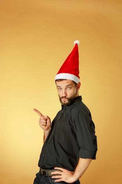 Ernsthafter weihnachtsmann, der eine weihnachtsmütze auf dem orangefarbenen studio trägt, das nach links zeigt Kostenlose Fotos