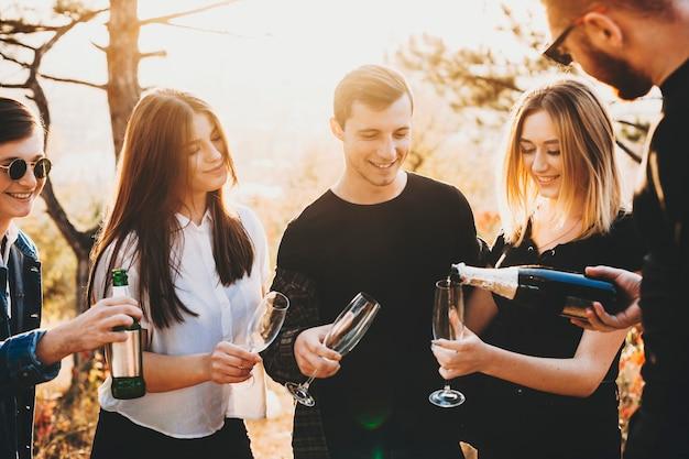 Ernte kerl, der champagner in gläser der jungen freunde gießt, während in der natur am sonnigen tag feiert Premium Fotos