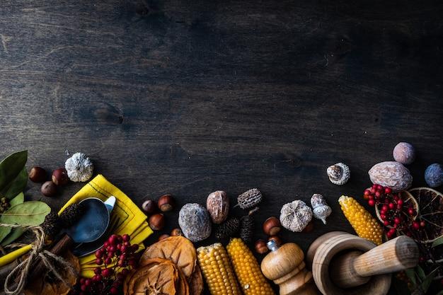 Erntedankfest oder herbstliches erntekonzept mit rahmen mit nüssen, beeren, gemüse und früchten auf dunkler holzoberfläche mit kopienraum Premium Fotos