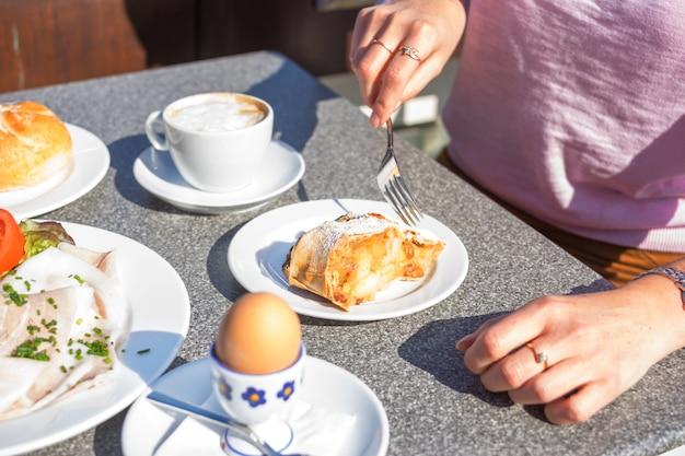 Ernten sie den schuss der frau ihr kontinentales frühstück essend Premium Fotos