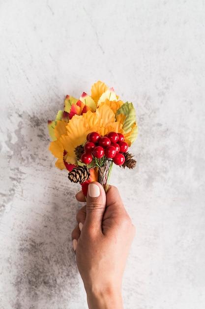 Ernten sie die frau, die herbstblumenstrauß auf schäbiger oberfläche hält Kostenlose Fotos