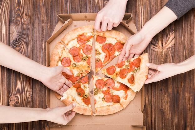 Ernten sie die hände, die pizza nehmen Kostenlose Fotos