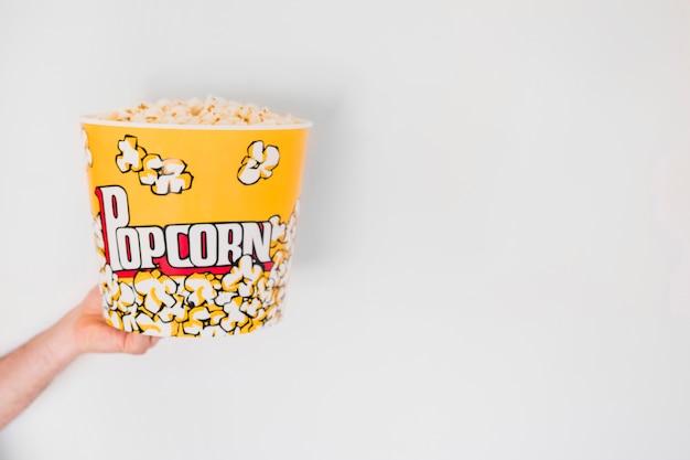 Ernten sie die hand, die eimer popcorn hält Kostenlose Fotos