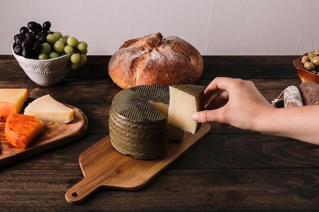 Ernten sie die hand, die käse nahe lebensmittel nimmt Kostenlose Fotos