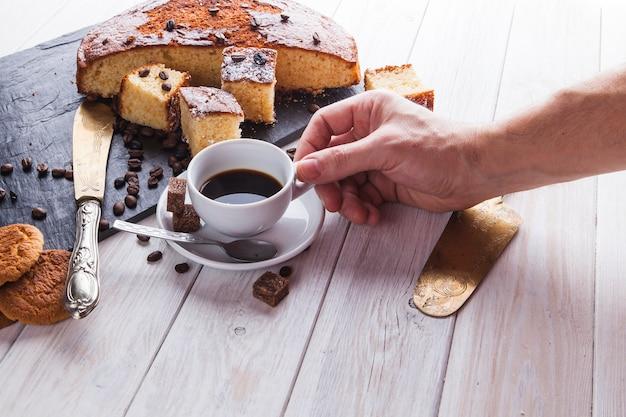 Ernten sie die hand, die kaffee nahe kuchen nimmt Kostenlose Fotos