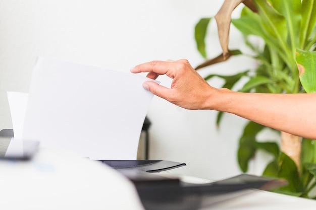 Ernten sie die hand, die papier vom bürodrucker nimmt Kostenlose Fotos