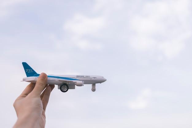 Ernten sie die hand, die spielzeugflugzeug hält Kostenlose Fotos