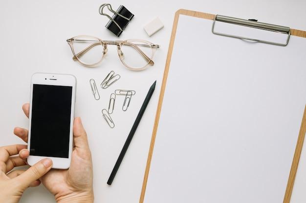 Ernten Sie die Hände, die Smartphone nahe Briefpapier halten ...