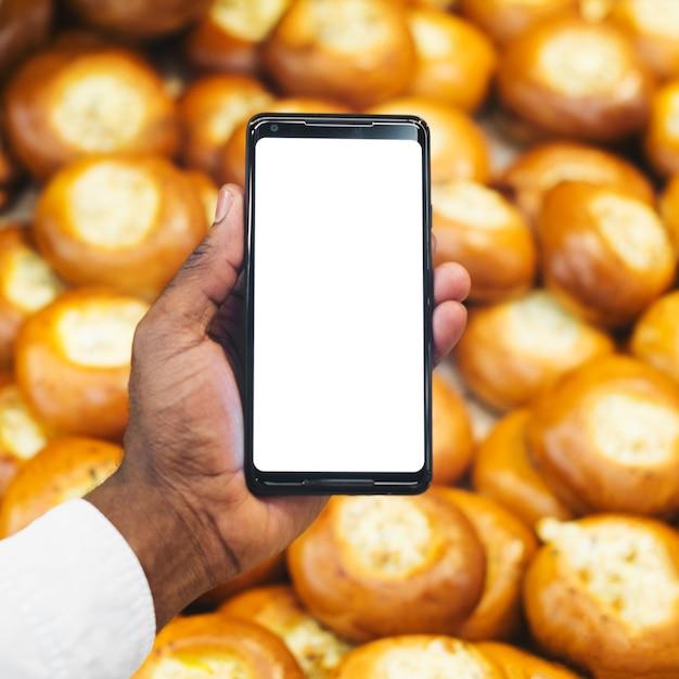 Ernten sie hand mit smartphone auf gebäckhintergrund Kostenlose Fotos