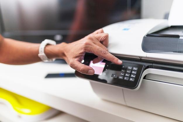 Ernten sie hand unter verwendung des druckers im büro Kostenlose Fotos