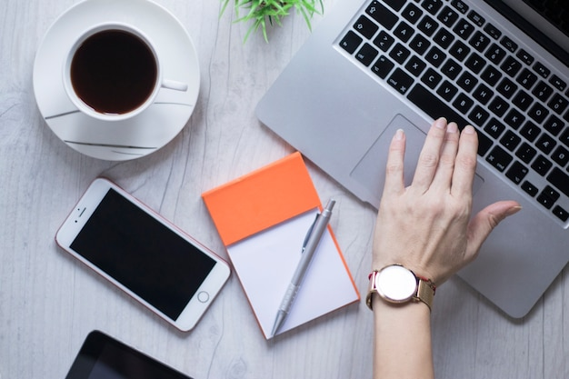 Ernten Sie Hand unter Verwendung des Laptops nahe Kaffee und Smartphone Kostenlose Fotos