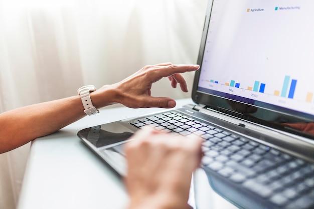 Ernten Sie Hände unter Verwendung des Laptops im Büro Kostenlose Fotos