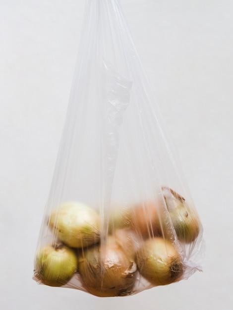 Ernten sie zwiebeln in der transparenten plastiktasche auf grauem hintergrund Kostenlose Fotos