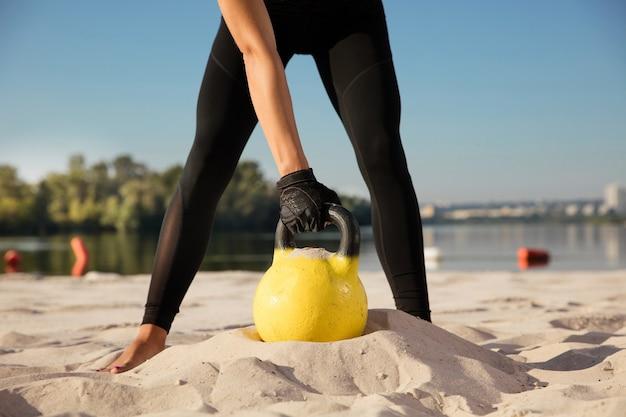 Ernteporträt der jungen frau, die mit gewichten am strand trainiert Kostenlose Fotos
