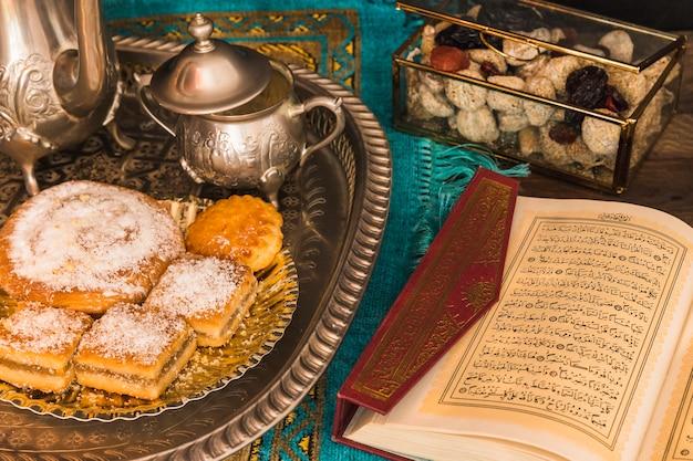 Eröffnet quran in der nähe von tee-set und süßigkeiten Kostenlose Fotos