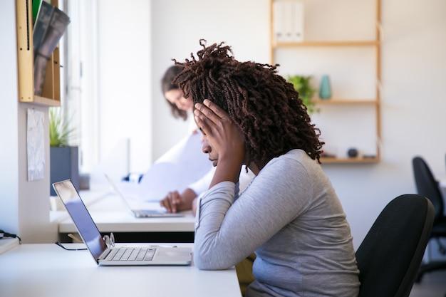 Erschöpfte afroamerikanerfrau, die laptop betrachtet Kostenlose Fotos