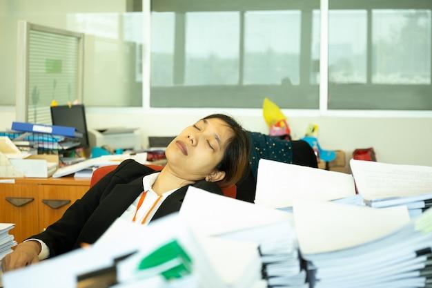 Erschöpfte geschäftsfrau, die auf schreibtisch im büro mit stapel des paperwok schläft. Premium Fotos