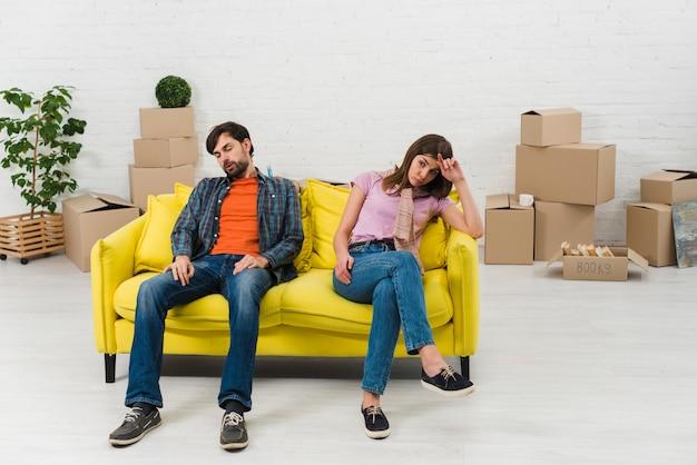Erschöpfte junge paare, die auf gelbem sofa mit beweglichen pappschachteln in ihrem neuen haus sitzen Kostenlose Fotos