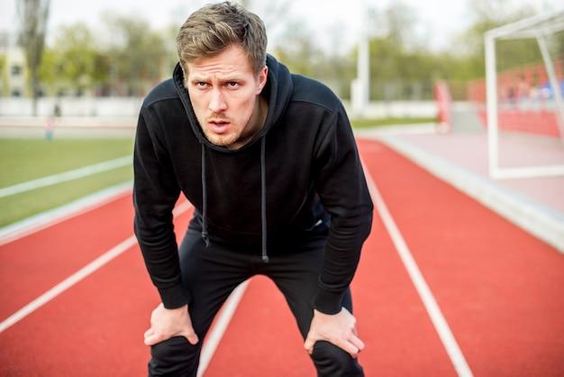 Erschöpfter junger männlicher athlet, der auf der rennstrecke ernsthaft schaut steht Kostenlose Fotos