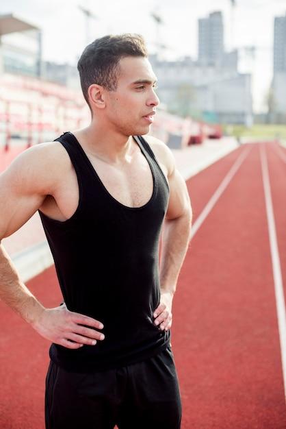 Erschöpfter junger männlicher athlet, der auf rennstrecke steht Kostenlose Fotos