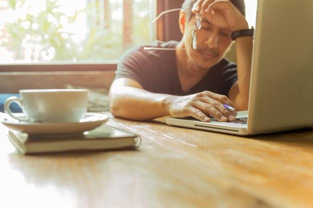 Erschöpfter mann, der an laptop mit augen arbeitet, schließen gegen fensterlicht. Premium Fotos