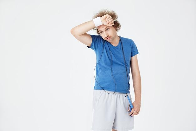 Erschöpfter mann, der sich nach dem training die stirn mit einem schweißband abwischt Kostenlose Fotos