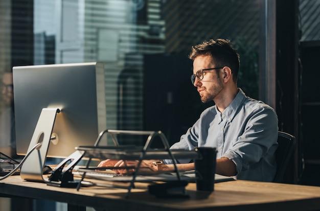 Erschöpfter mann, der überstunden im büro arbeitet Premium Fotos