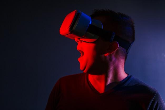 Erschrockener junger mann in vr 3d gläsern auf dunklem hintergrund mit roter blauer beleuchtung Kostenlose Fotos