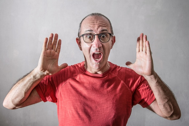 Erschrockener mann mit den händen auf gesicht Premium Fotos